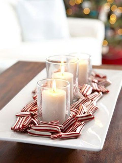 a Christmas centerpiece of a square dish with candles and candy canes on it is a lovely and easy decor idea to recreate
