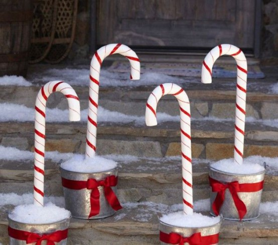pretty outdoor Christmas decor done with buckets with faux snow and candy canes is a very fun and cool idea