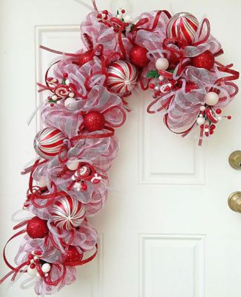 a red and white ribbon and ornament candy cane shaped wreath is a very creative alternative to a usual Christmas wreath