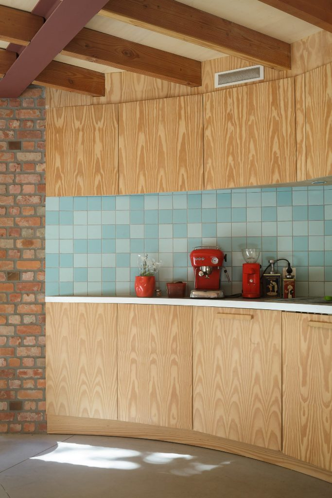 Two-tone blue tiles form a kitchen splashback and   plus bright red appliances help to create a mid-century modern feel