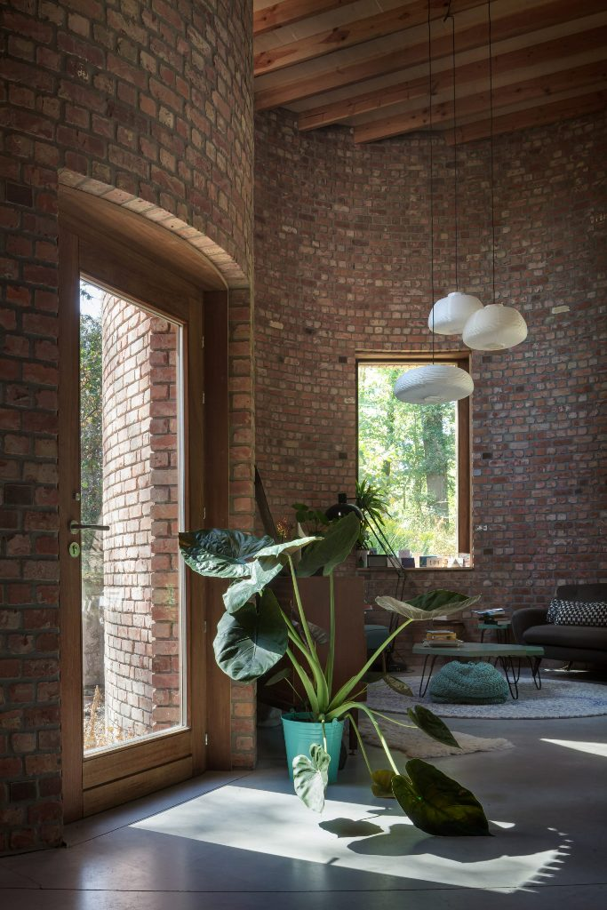 Glass doors and large windows brign much natural light in, there are statement plants add coziness here
