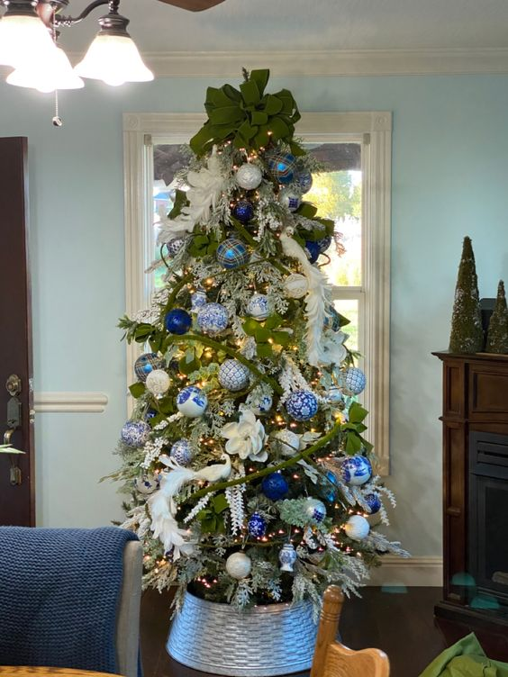 a beautiful Christmas tree with white feathers and fabric blooms, blue and white ornaments, a large green bow on top is amazing