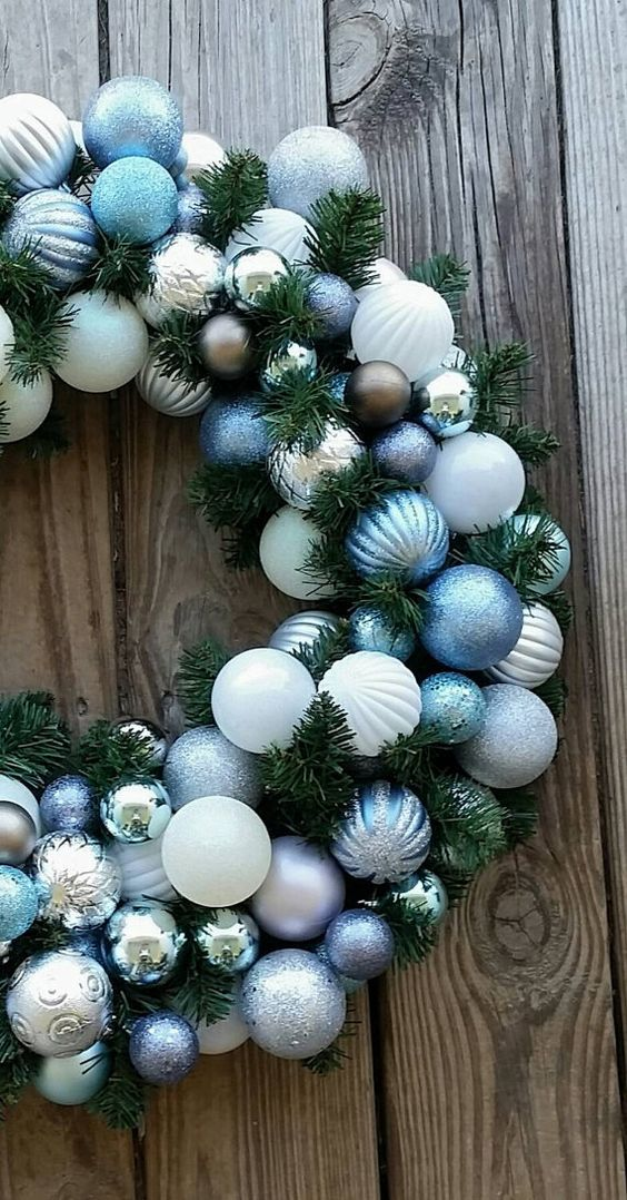 a Christmas wreath decorated with blue white, silver and chocolate ornaments looks very elegant and very chic