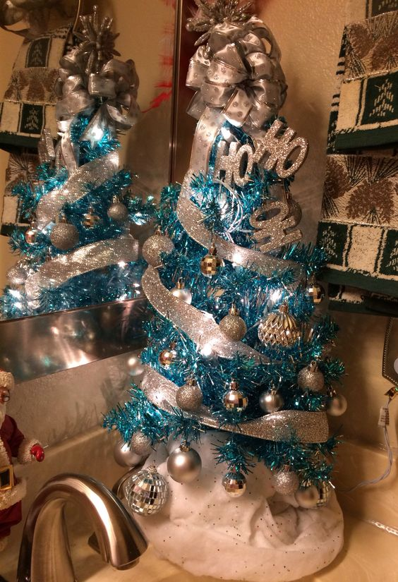 a blue Christmas tree with silver and glitter ornaments, glitter ribbons and a bow on top plus letters is amazing as an additional one