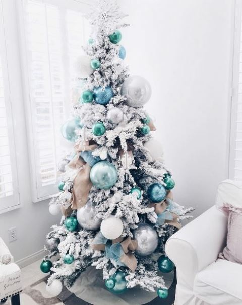 a flocked Christmas tree with green, blue and silver ornaments of various sizes for a lovely and very modern look