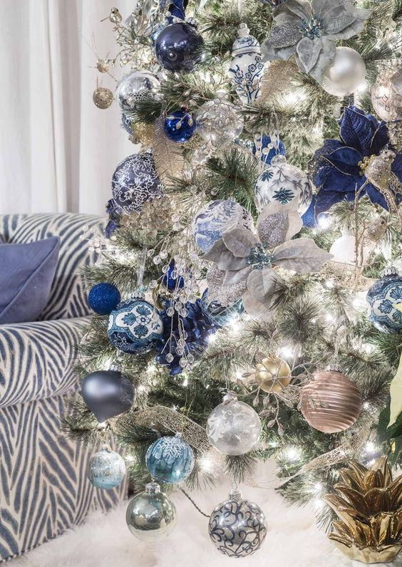 a silver Christmas tree with silver, light blue and navy ornaments, fabric blooms and ribbons is a very chic and glam idea