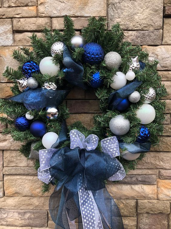 an elegant Christmas wreath with white, silver, navy ornaments, white and navy ribbon bows and ribbons is amazing