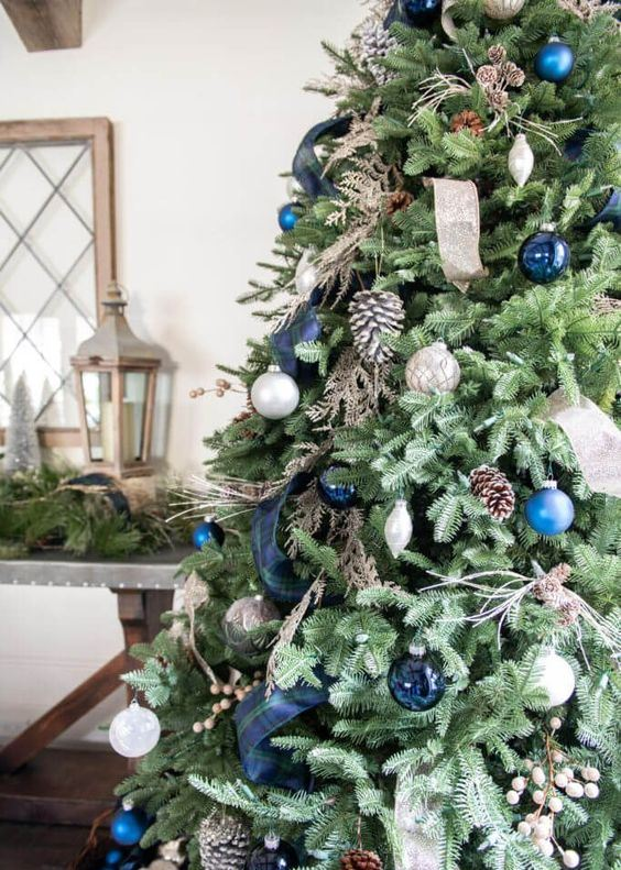 beautiful and natural Christmas tree decor with pinecones, silver, blue and navy ornaments and ribbons is very chic