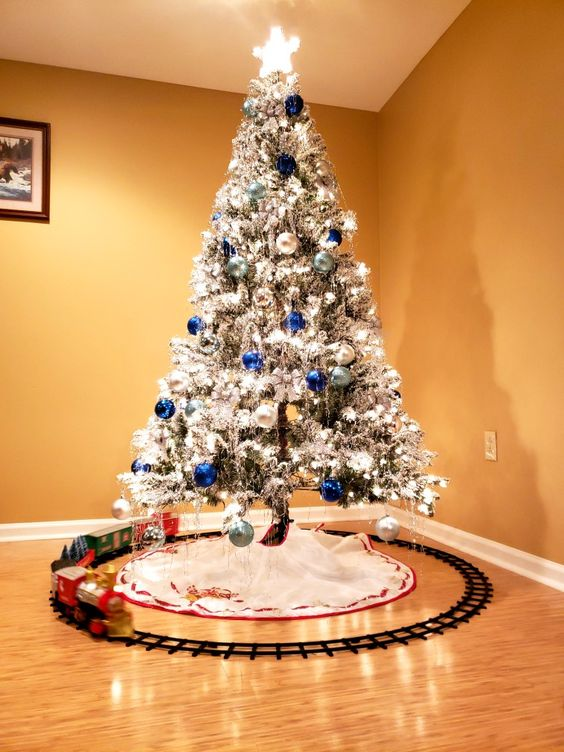 a flocked Christmas tree with lights, silver, navy and light blue ornaments is very beautiful, bold and shiny and looks amazing