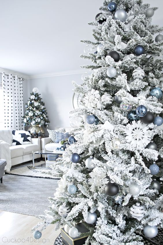 a flocked Christmas tree with blue, silver and black ornaments is a lovely and chic piece that looks frozen and elegant