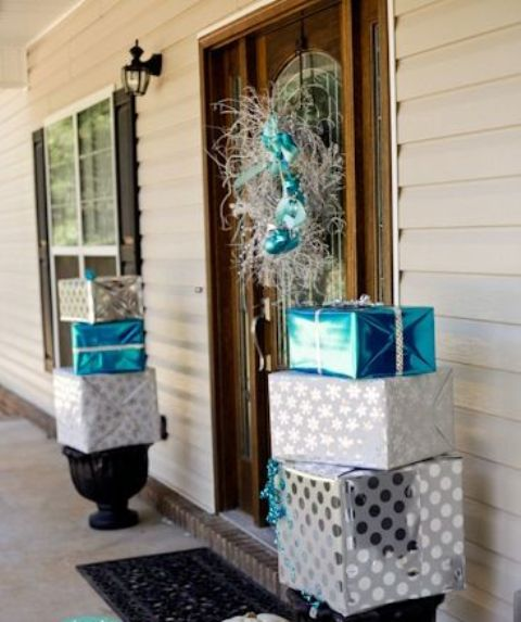 front porch Christmas decor with stacked silver and blue gift boxes and with a silver and blue wreath on the front door is amazing