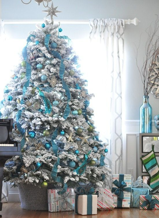 a pretty blue and silver Christmas tree with ribbons, ornaments, some green touches and gifts under the tree is very refined and chic