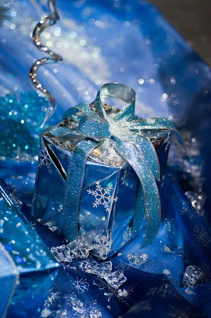a Christmas gift wrapped in blue paper with snowflakes and with a large bow is a cool and bright idea to rock