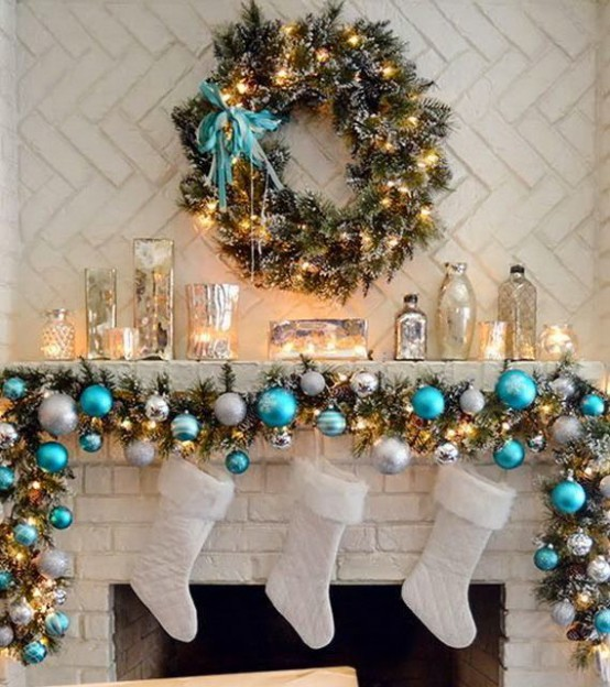 a fir garland with blue and silver ornaments plus lights, candles in mercury glass candleholders and a greenery wreath with lights and a turquoise bow
