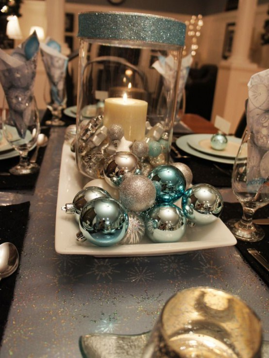 a sparkling Christmas centerpiece of a plate with blue and silver ornaments and a candle lantern with blue glitter is very chic and easy to recreate