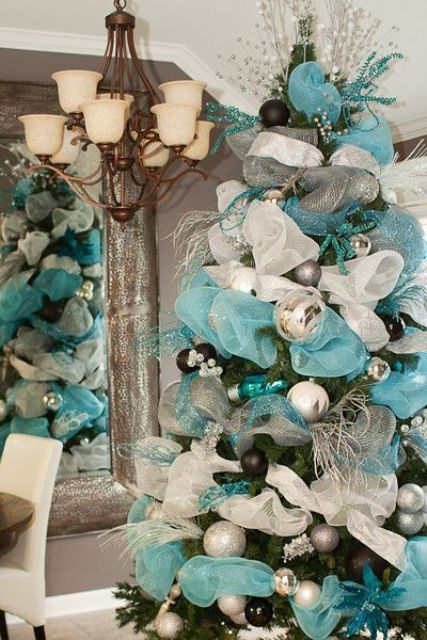 lush blue and silver Christmas tree decor with ribbons, ornaments, twigs, branches and beads is very formal and chic