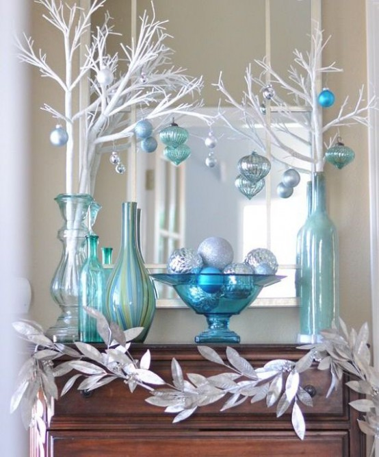 beautiful blue, turquoise and silver Christmas decor with vases, white branches, blue and white ornaments and a garland of silver leaves