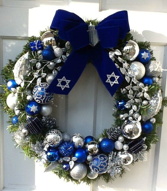 a bright Christmas wreath with bold blue, silver and white oraments and a large navy velvet bow on top is an amazing decoration