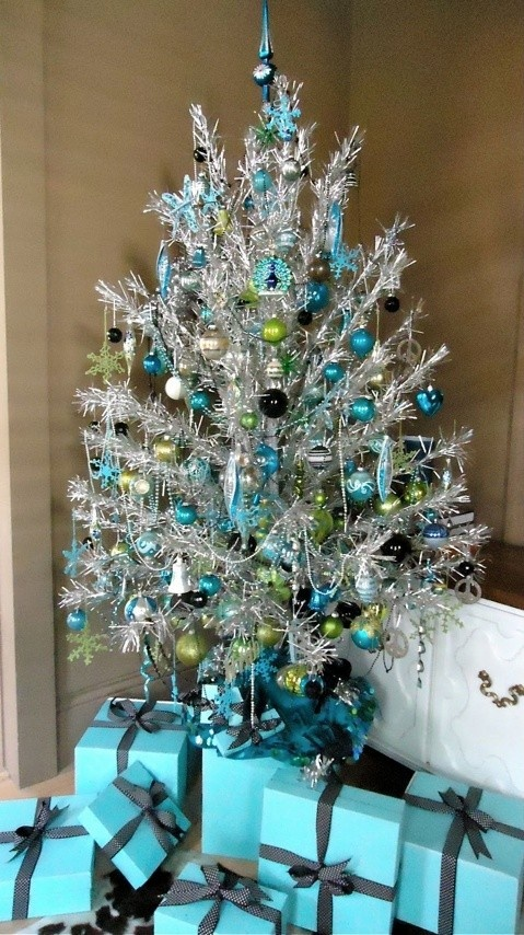 a silver Christmas tree with blue, green and silver ornaments and beaded garlands is a very bright and shiny idea