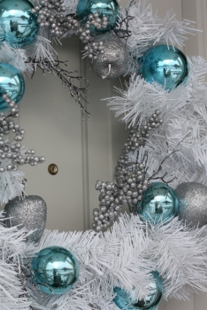 a white Christmas wreath with beads, silver and tiffany blue ornaments is a cool outdoor decoration to rock