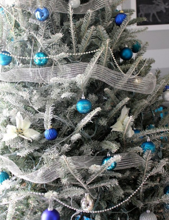 a frozen Christmas tree decorated with silver ribbons, blue, navy and black ornaments looks very spectacular and bold