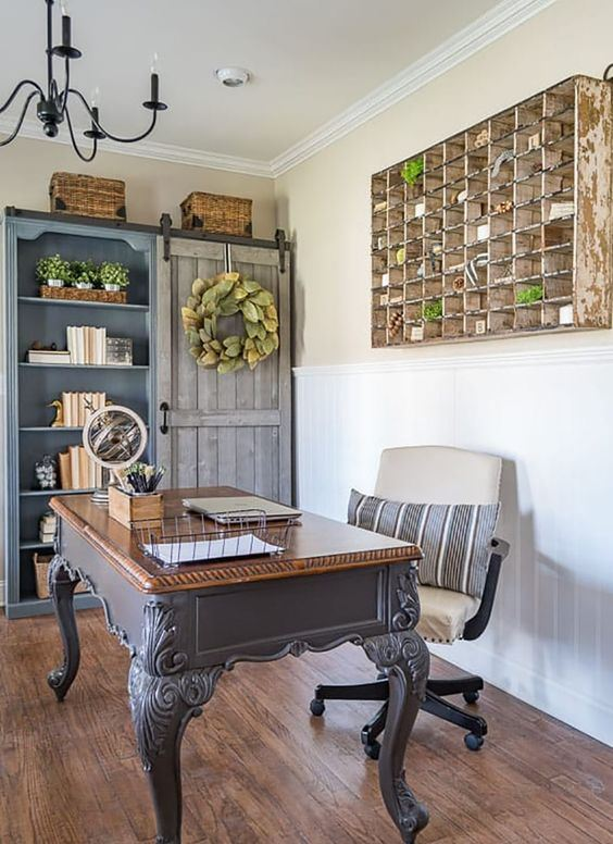 a French farmhouse home office with a built-in blue storage unit, a vintage desk, a leather chair and a storage unit on the wall