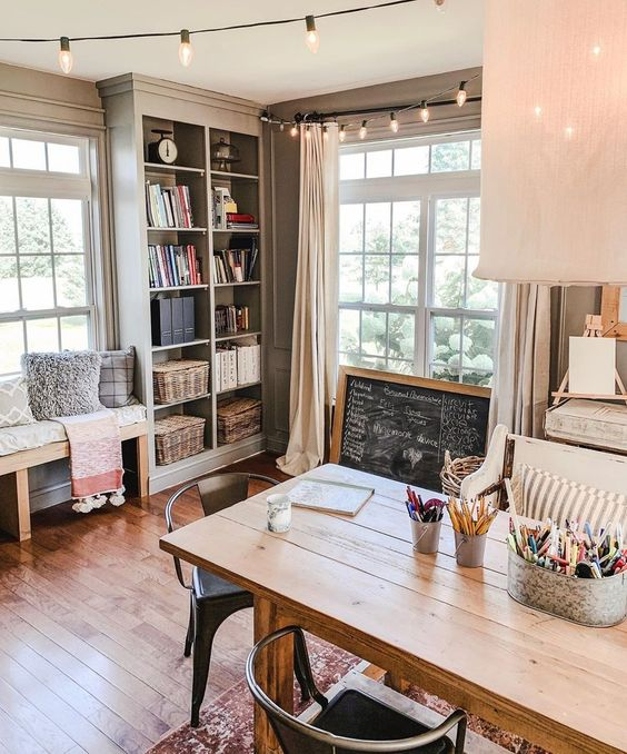 a cottage home office with a wooden desk, a chalkboard sign, a built-in storage unit and a bench is very welcoming and cool