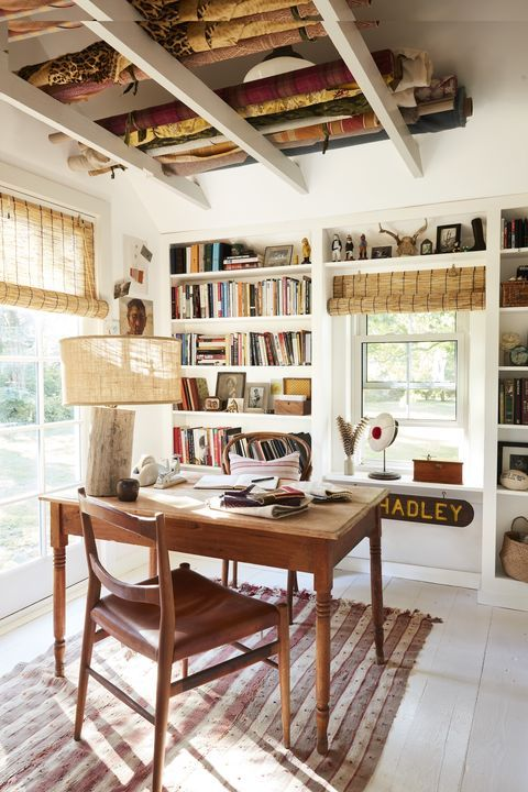 a catchy farmhouse home office with built-in storage units and shelves, a wooden desk and chair, a rustic lamp and woven shades
