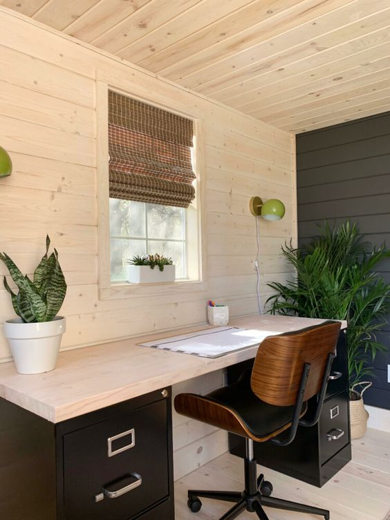 a modern farmhouse home office with the walls, ceiling and floor clad with wood, a contrasting desk and potted greenery