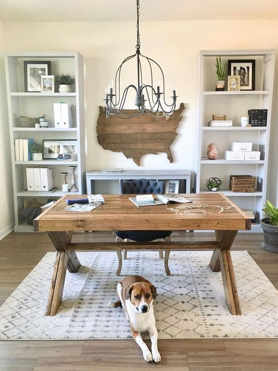 a cozy farmhouse home office with storage units, a wooden desk, a state wal art, a printed rug and a vintage chandelier