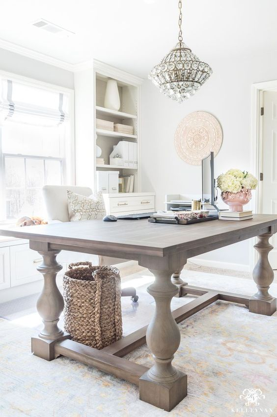 a light-filled farmhouse home office with a large wooden desk, neutral storage units, a crystal chandelier and neutral blooms
