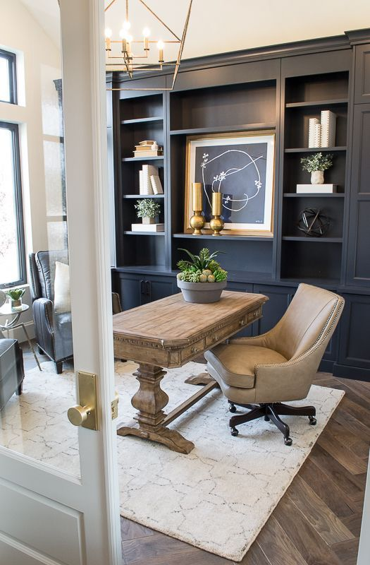 a modern farmhouse home office with a navy storage unit that takes a whole wall, a wooden desk, leather chairs and a refined gold chandelier