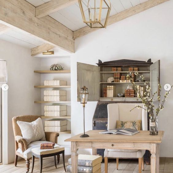 a refined farmhouse home office with a wooden desk, vintage chairs, a storage niche and open shelves is welcoming