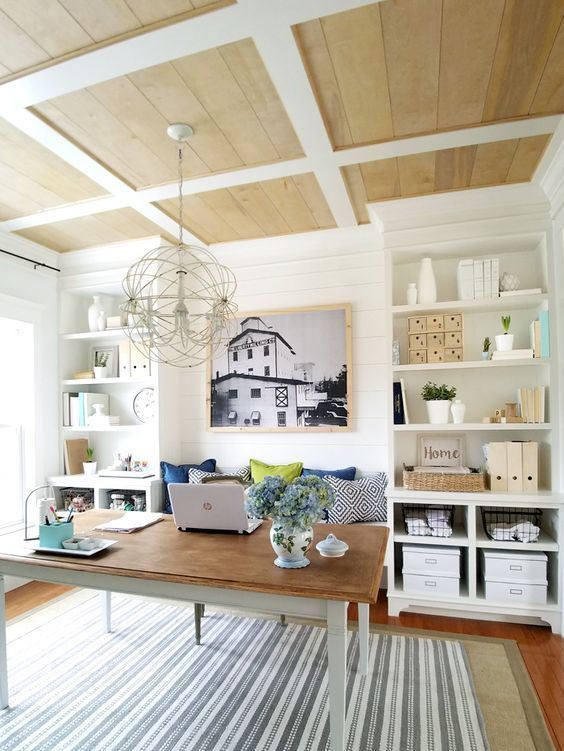 a farmhouse home office with built-in storage units, a simple desk and a built-in bench to sit on, a sphere chandelier