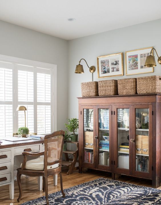 a vintage farmhouse home office with a white desk, a rattan chair and a storage unit, baskets and brass scones