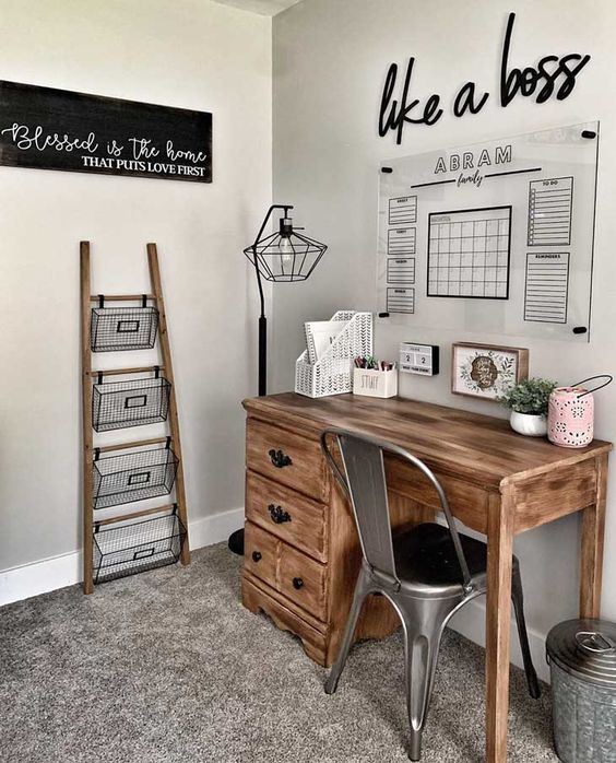 a small and cozy farmhouse home office with a wooden desk, a metal chair, a ladder and wire basket storage unit and an acrylic board