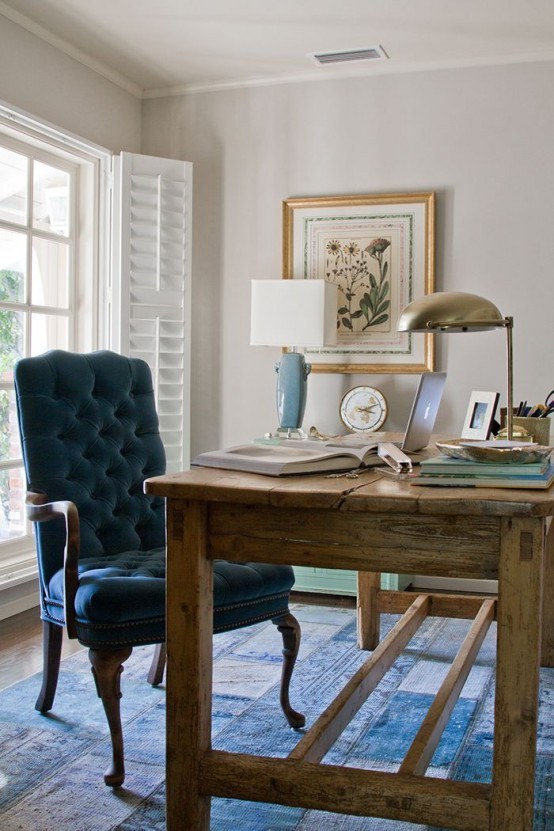 an inviting farmhouse home office with a wood and metal desk, a white chair, storage units and a large clock