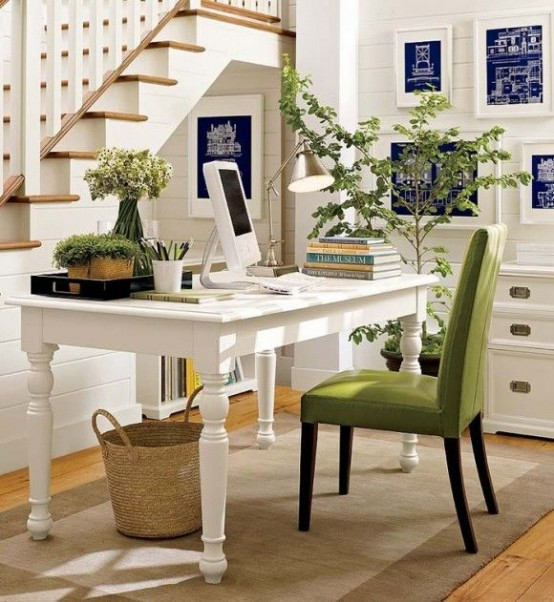 a pretty and light-filled modern farmhouse home office in white, with beadboard on the walls, a vintage desk and a green chair and some greenery to refresh the space visually