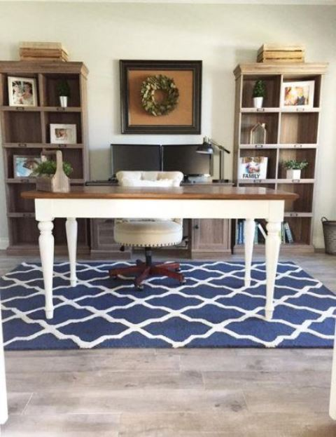 a vintage farmhouse home office with white walls, open storage units, a vintage desk, a blue printed rug, a leather chair and some art