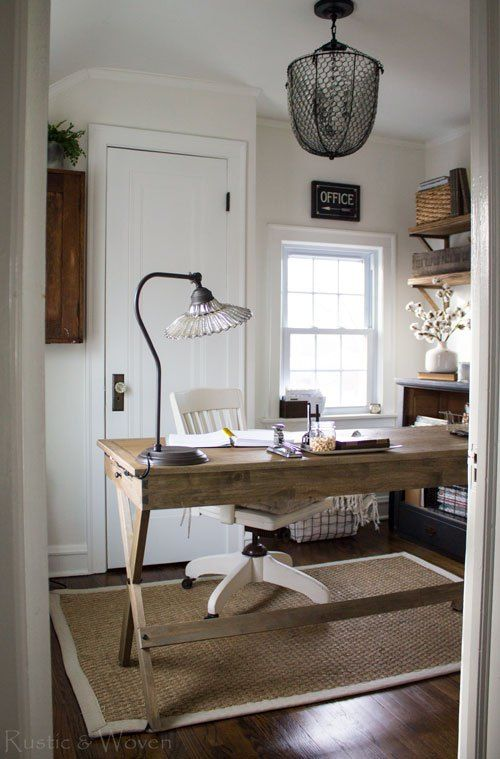 a welcoming farmhouse home office with a wooden desk, a jute rug, open shelves, a metal chandelier and a crystal lamp