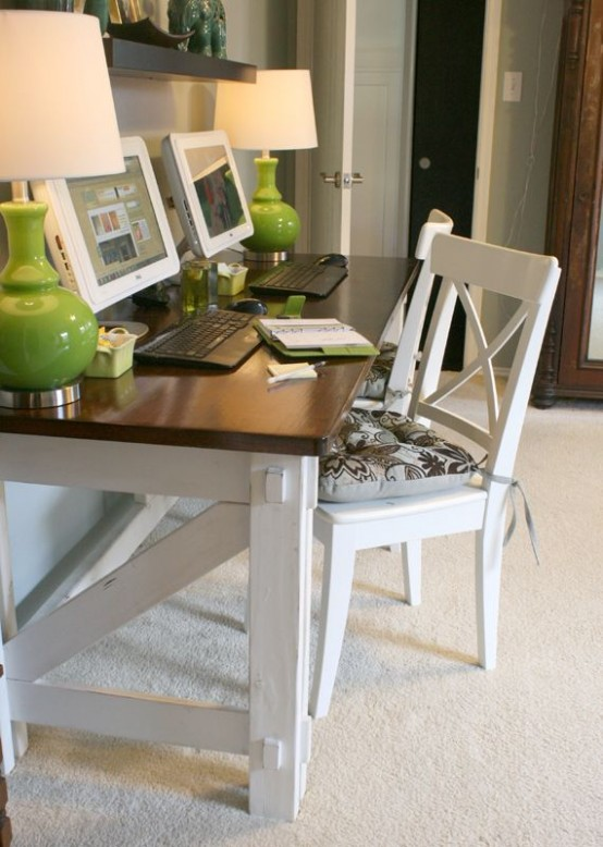 a modern farmhouse home office in neutrals, with a wooden desk with a black tabletop, a chair, green table lamps and some decor on the dark shelf