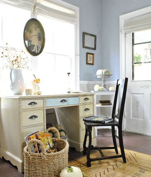 a vintage farmhouse home office with pastel blue walls, a shabby chic desk, a dark chair, vintage artworks and baskets with pumpkins for fall decor