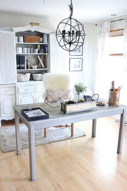 a vintage farmhouse home office with a large white storage unit, a neutral desk, a sphere chandelier and a fluffy fur chair
