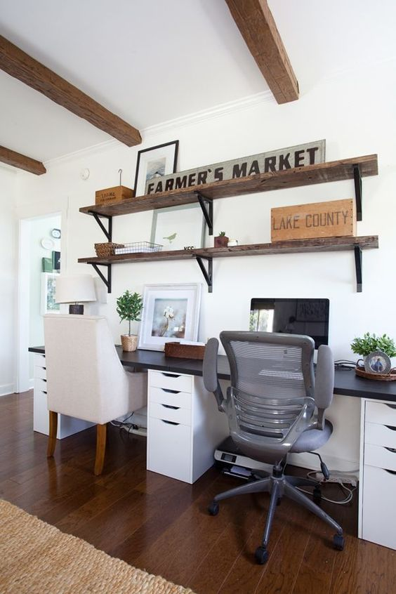 a simple farmhouse home office with industrial shelves, a shared desk, modern chairs and some potted greenery