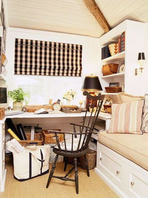 a neutral and cozy farmhouse home office with a built-in desk, bookshelves and a daybed, a vintage chair, a black lamp and a plaid curtain