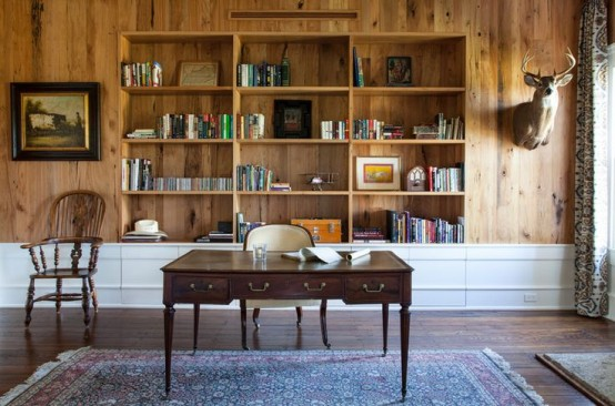 a farmhouse home office with a wood clad wall, built-in bookshelves in a niche, a vintage desk and some chairs plus a bold rug