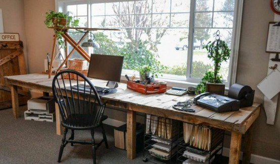 a farmhouse home office with a super long wooden desk with open storage units, a vintage chair, potted greenery and cool relaxing views