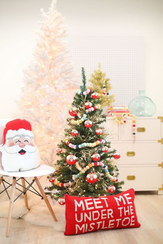 a Christmas tree with lights, colorful pompom garlands, a red pillow and a Santa one will add a fun and dreamy holiday feel