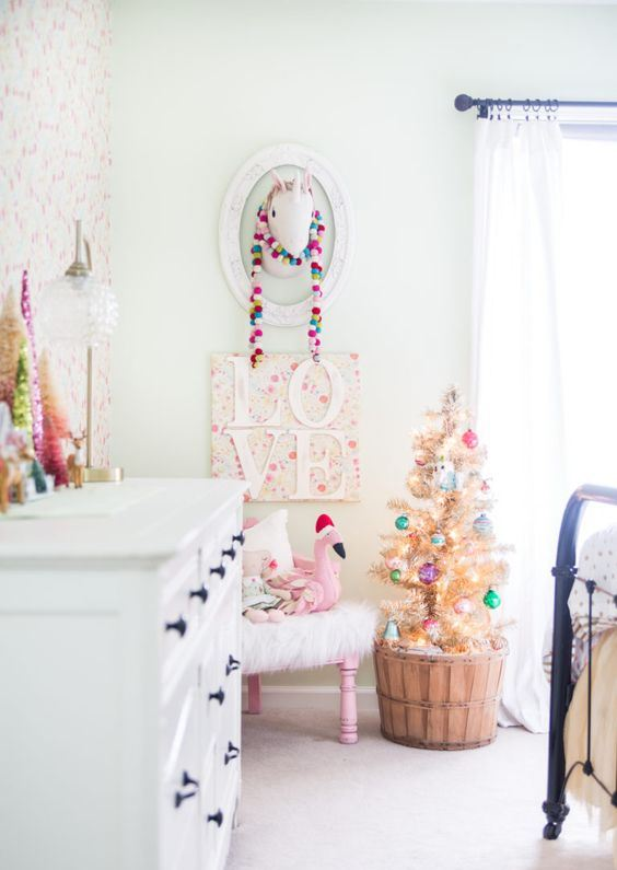 a colorful pompom garland, a Christmas tree with lights and bright ornaments and some tinsel trees on the dresser for a holiday feel