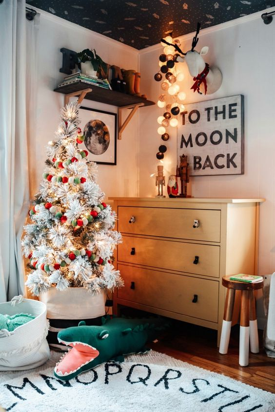 a flocked Christmas tree with lights and red, white and green pompom ornaments is a pretty and cool idea for holidays